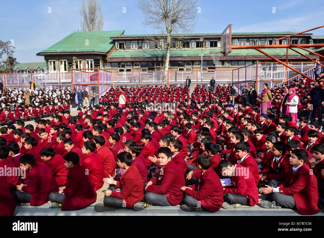 Srinagar, India. 10th Mar, 2018. Kashmiri students attend the morning assembly in their school premises after a - Stock Image