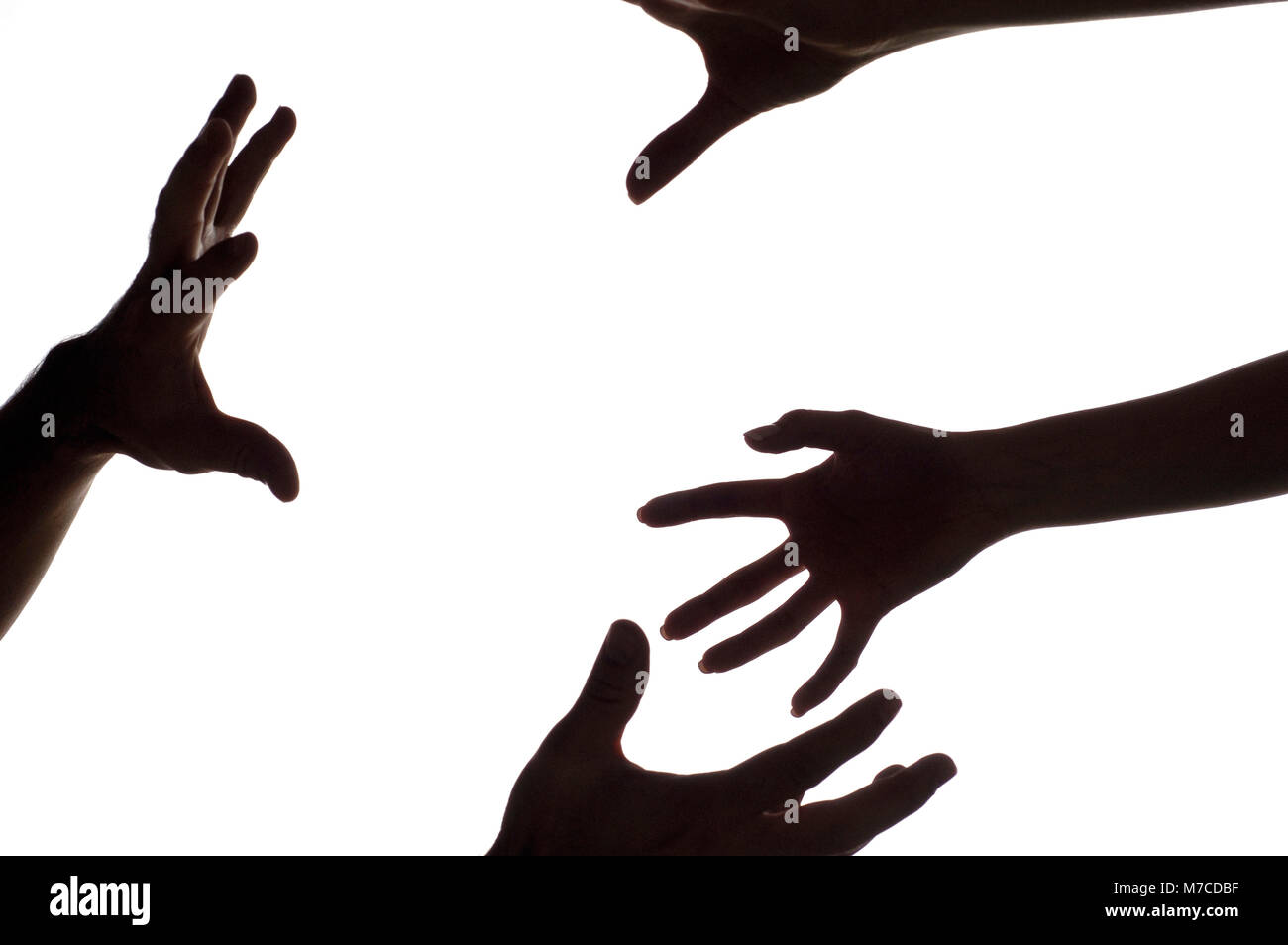 Close-up of a woman's hands reaching for a man's hands - Stock Image
