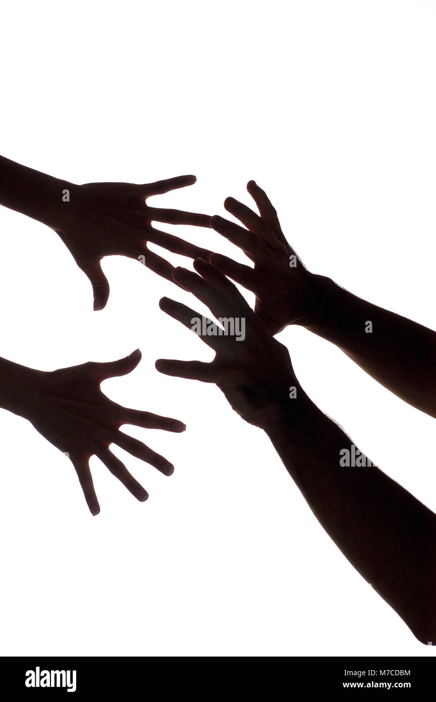 Close-up of a woman's hands reaching out for a man's hands - Stock Image