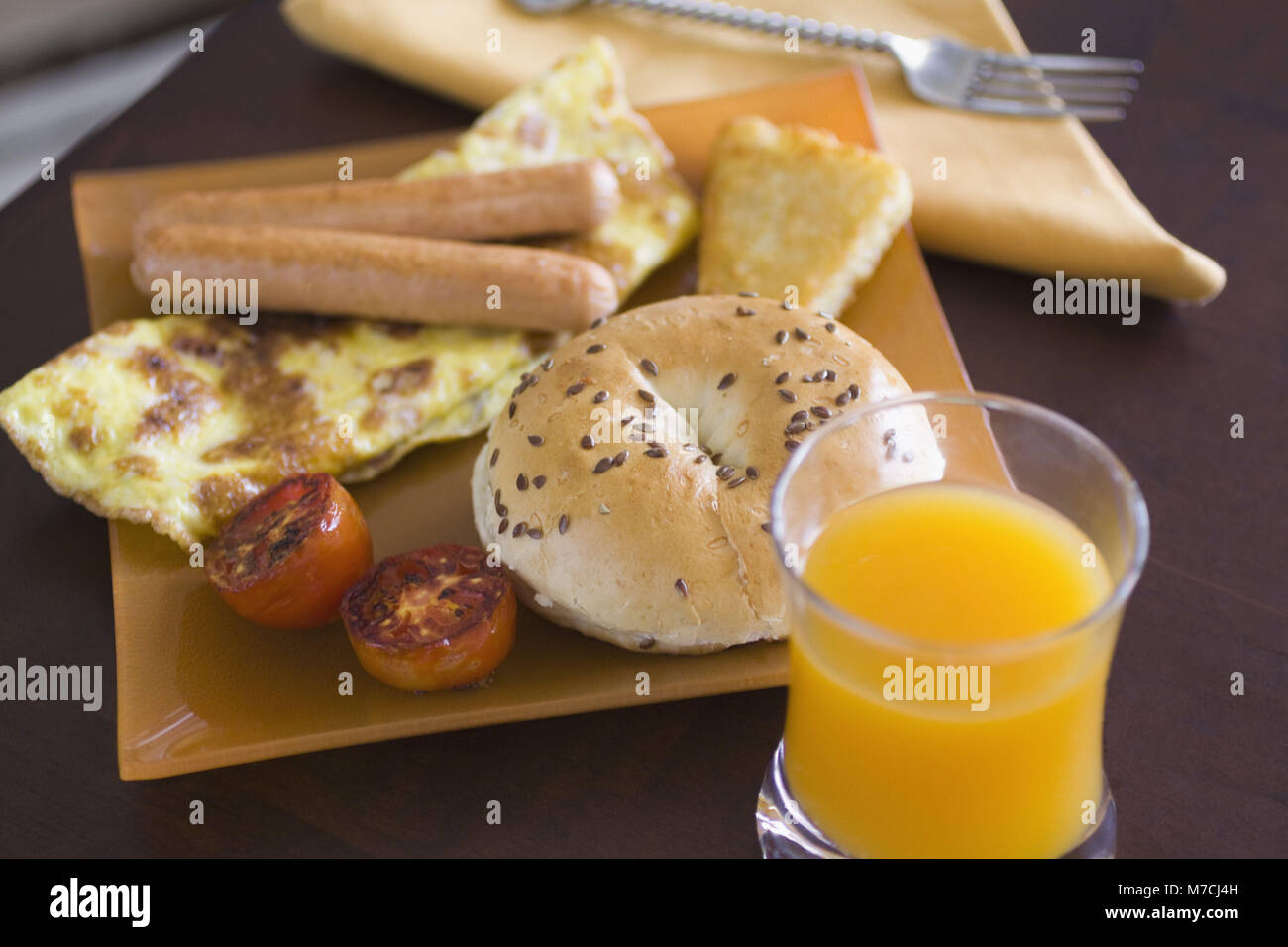 High angle view of an omelet served with frankfurters and a bagel - Stock Image