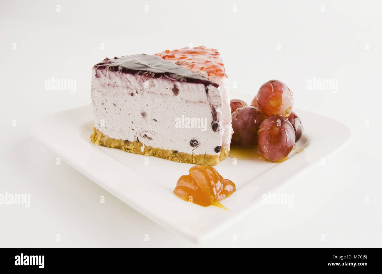 Close-up of two slices of cheesecake with glazed grapes - Stock Image