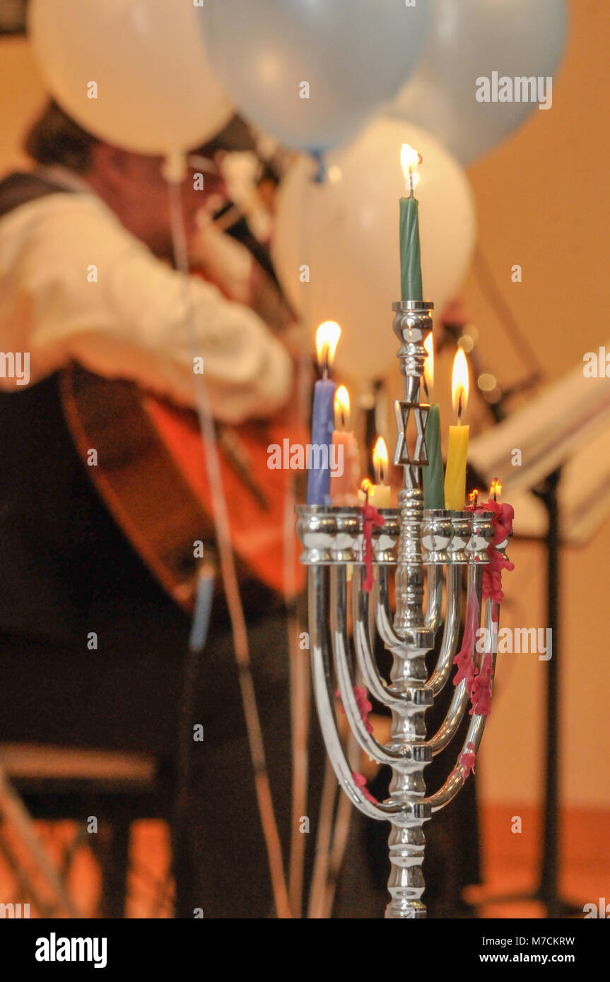 A Menorah  with eight candles burns at a Jewish holiday concert.  Candles in foreground and Jewish band blurred - Stock Image