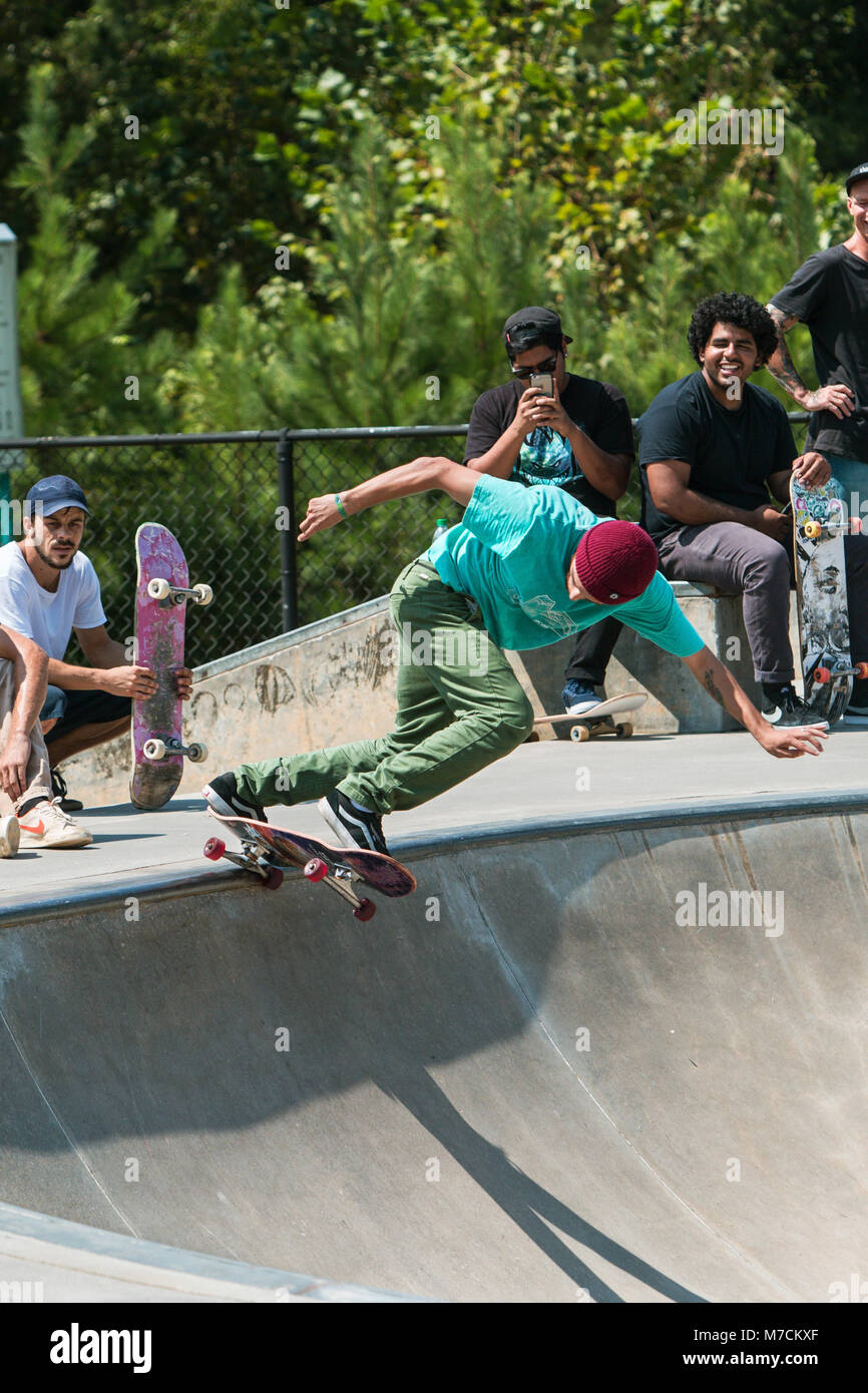 A young adult skateboarder drops in at the bowl as other skateboarders watch, at Settles Bridge Skateboard Park - Stock Image