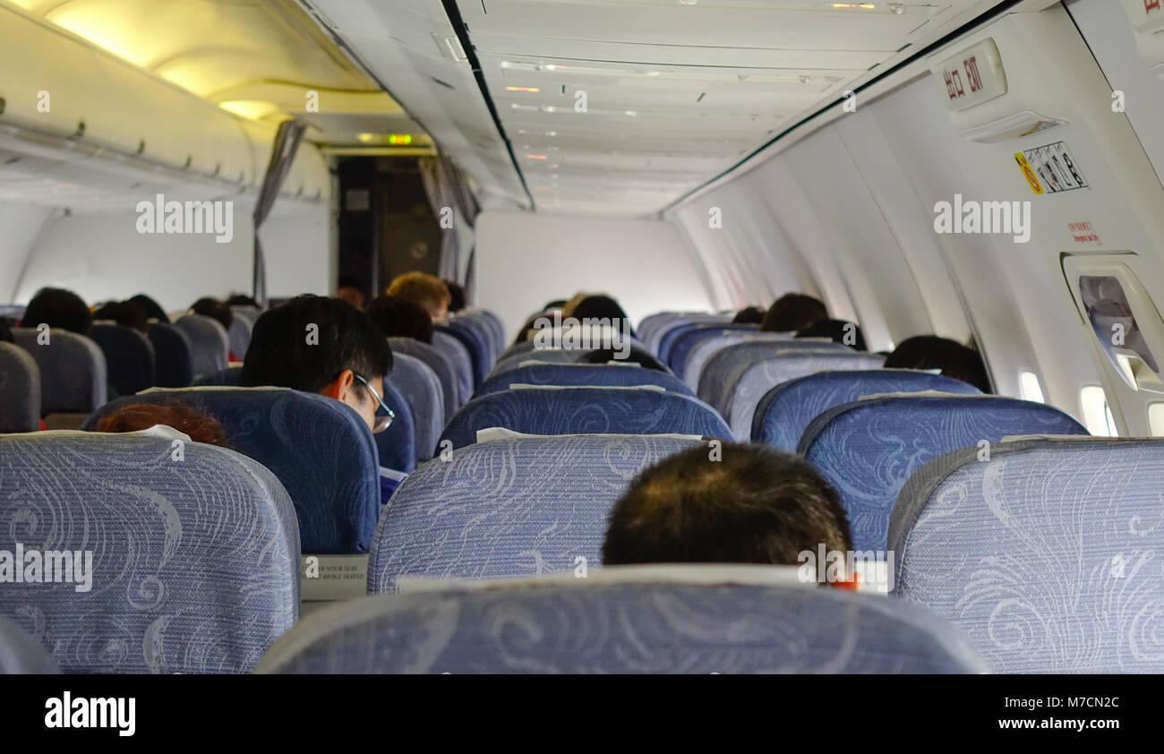 Beijing, China - Feb 17, 2018. Passengers sitting on a civil aircraft at Beijing Capital Airport, China. - Stock Image