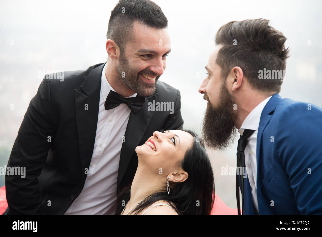 two men and a woman in love triangle, smiling resumed in the foreground - Stock Image