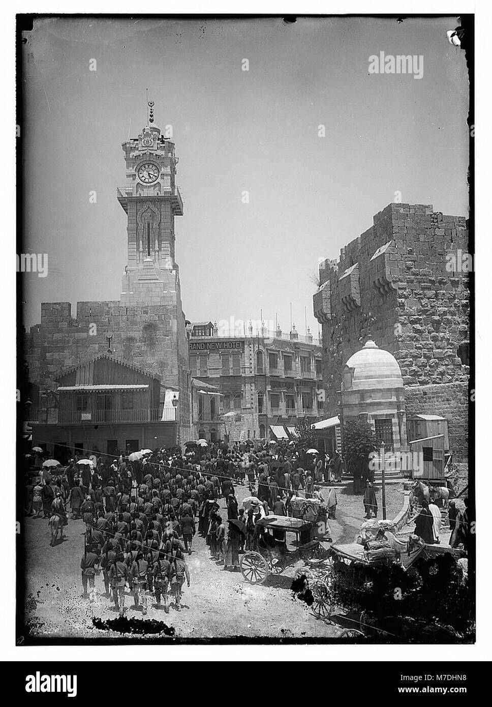 Marching in front of Am. (i.e., American) Colony store. Grand New Hotel (Jerusalem) LOC matpc.06380 - Stock Image
