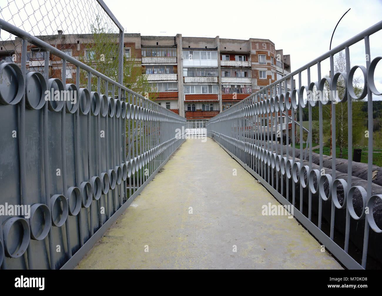 End of pedestrian bridge over suburban road and curved continuation of wooded recreational trail - Stock Image