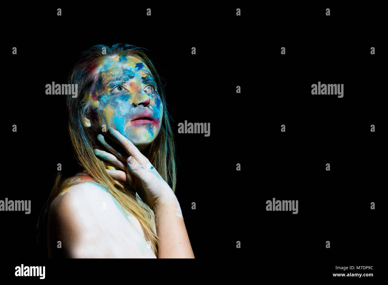 A woman with her face painted in an abstract style poses for the camera - Stock Image