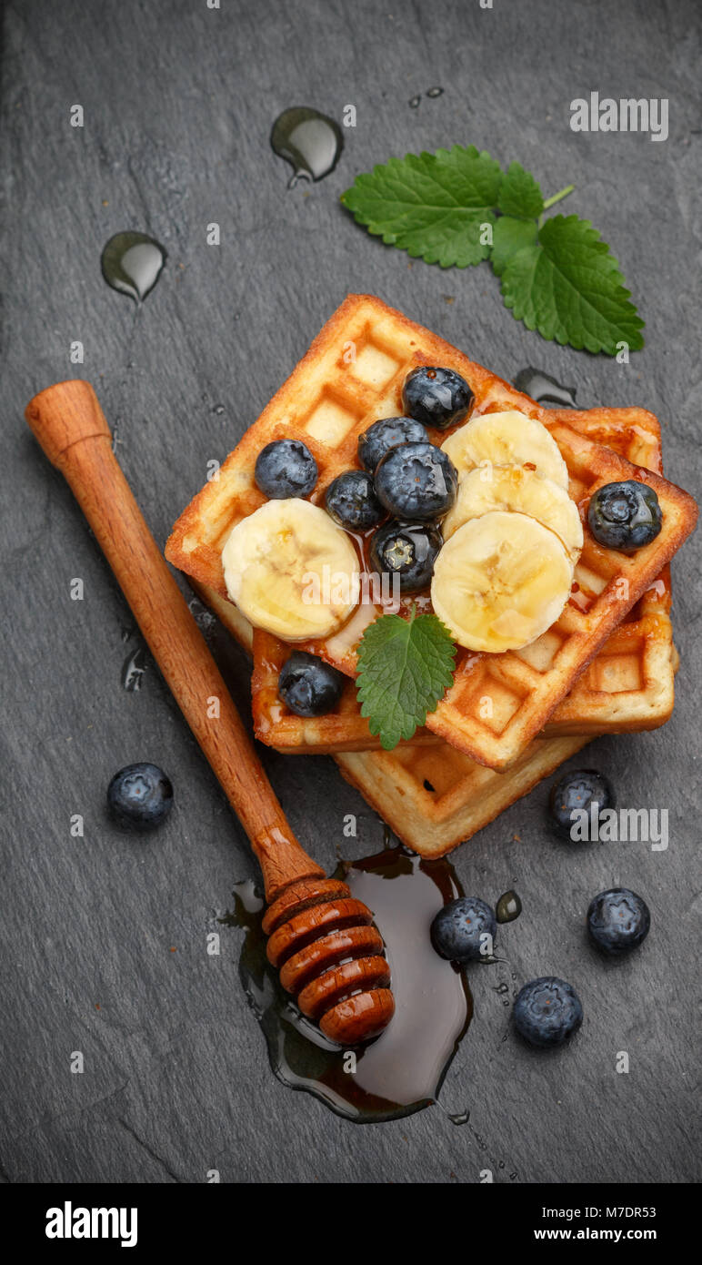 Traditional Belgian waffles with blueberries, banana and honey on a black slate plate. Gourmet Breakfast. Selective - Stock Image