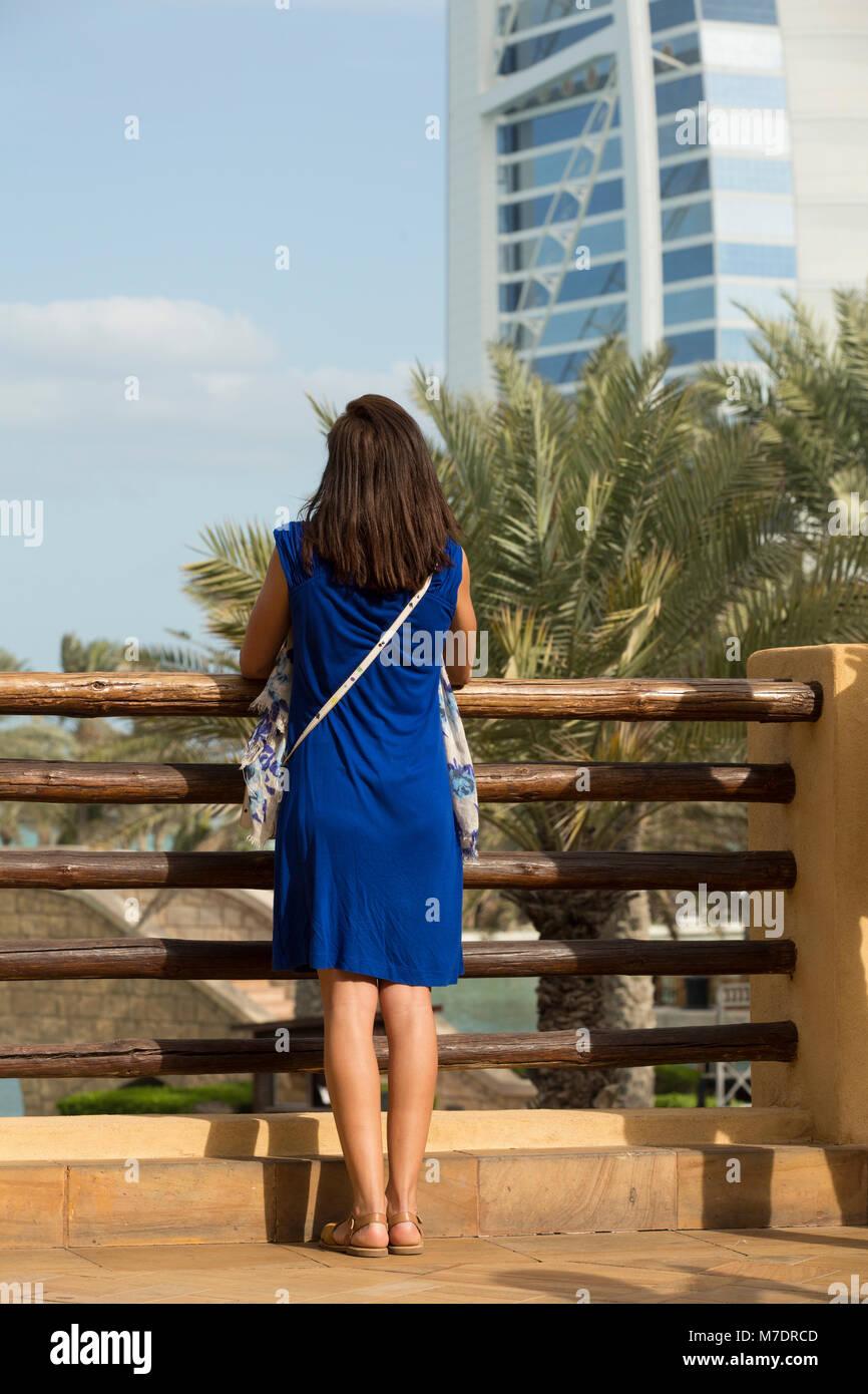Female tourist looking at Burj Al Arab from Madinat Jumeirah Dubai UAE - Stock Image