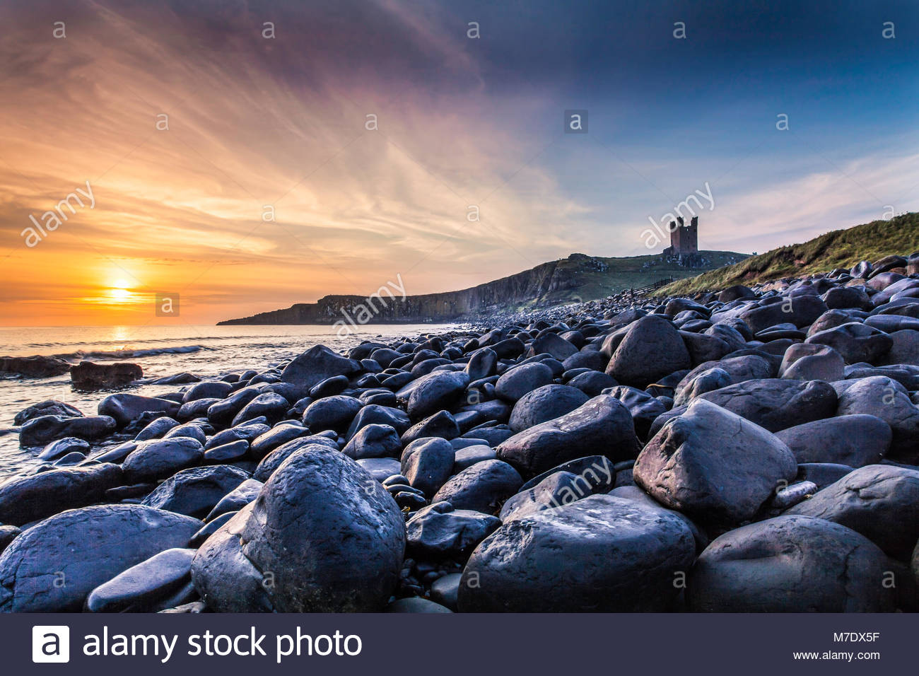 Dunstanburgh castle in Northumberland at dawn. - Stock Image
