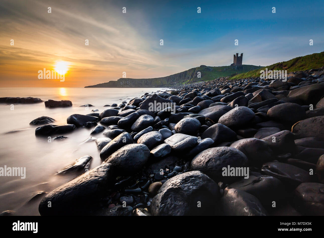 Dunstanburgh castle in Northumberland above the famous boulders in Embleton Bay. - Stock Image