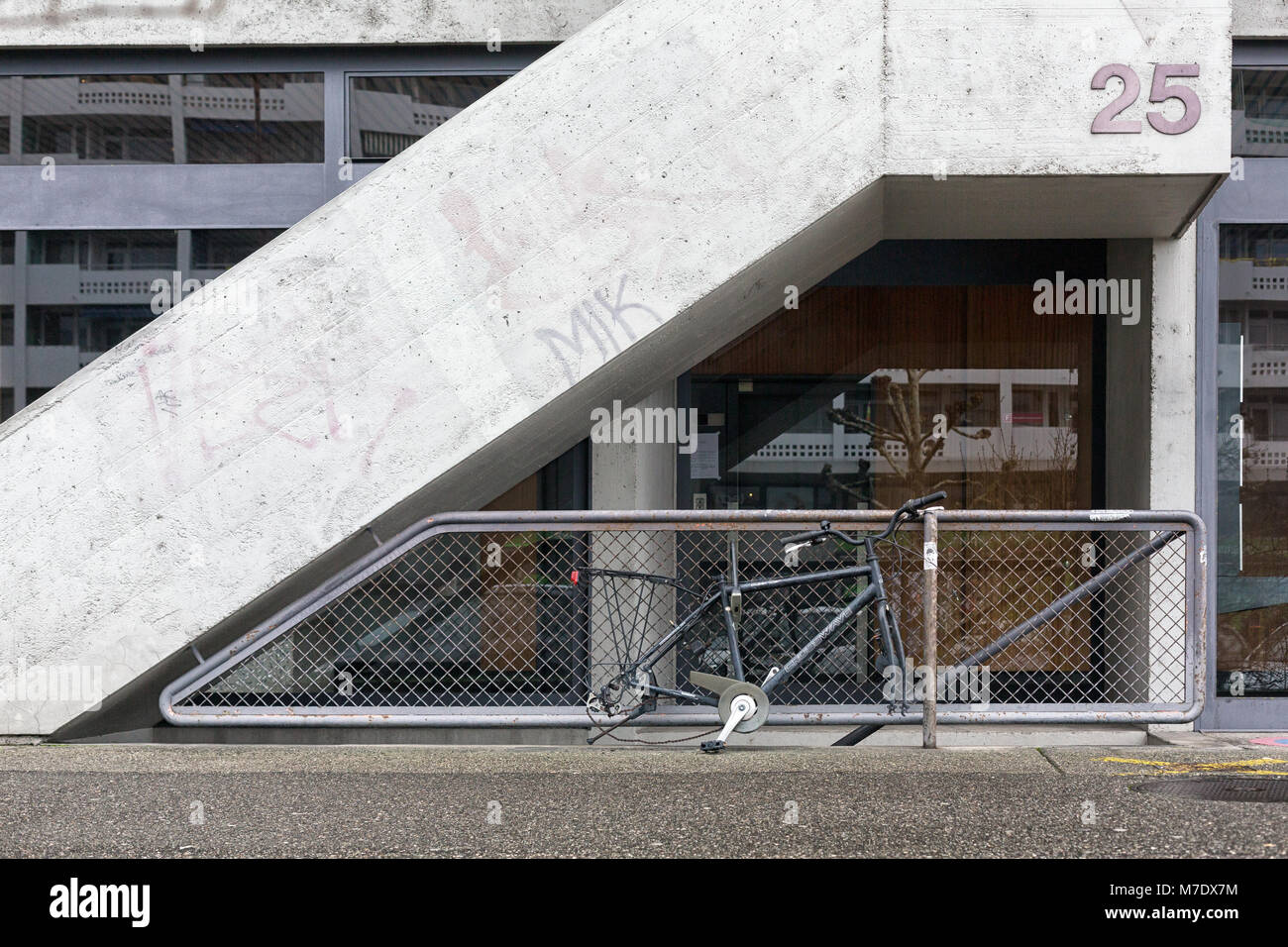 A lost or stolen bike that misses the wheels attached to a barrier of a building in town. - Stock Image