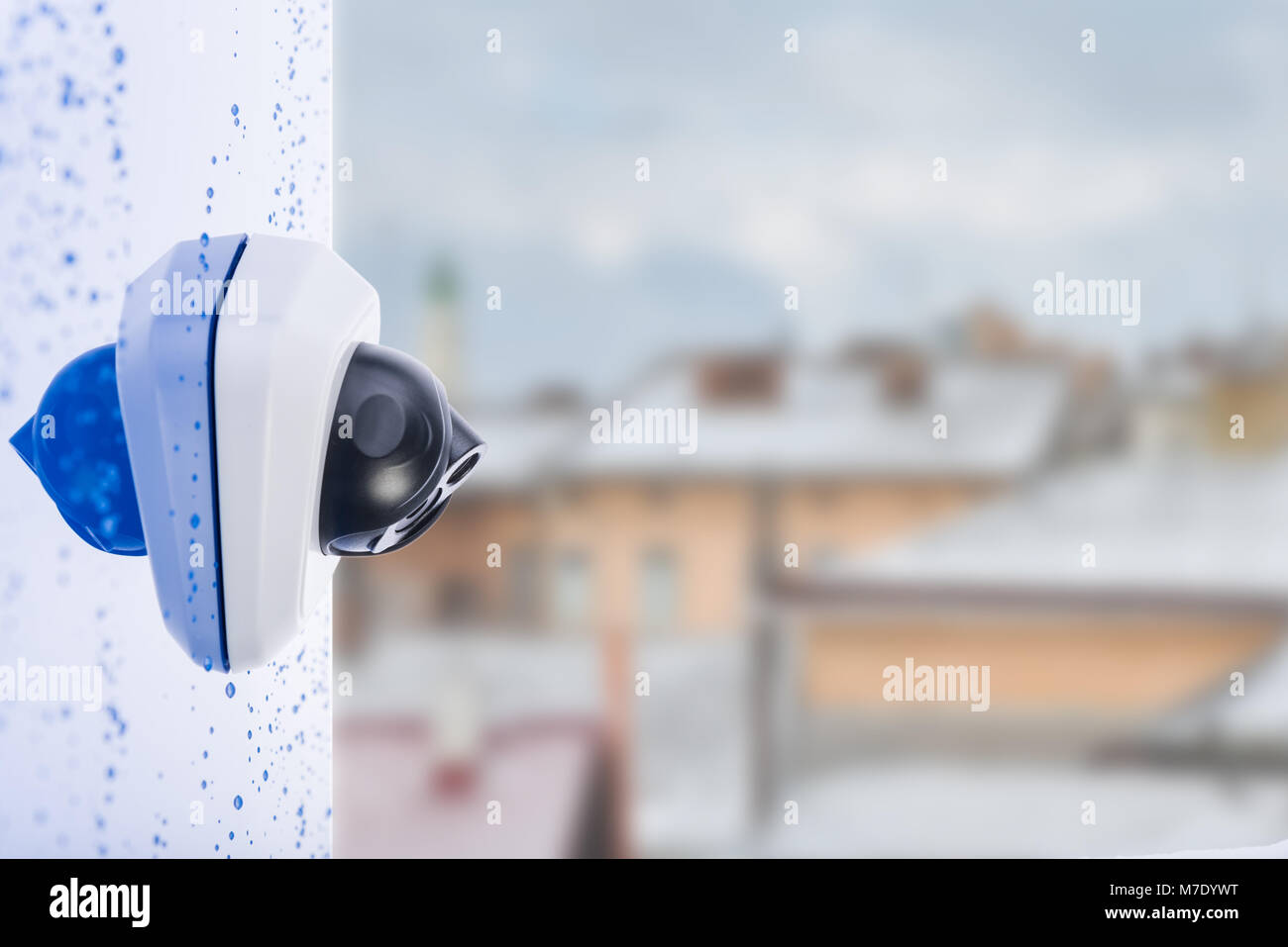IP Camera on the wet wall, blurred city background, space for text. Concept - technology and security - Stock Image