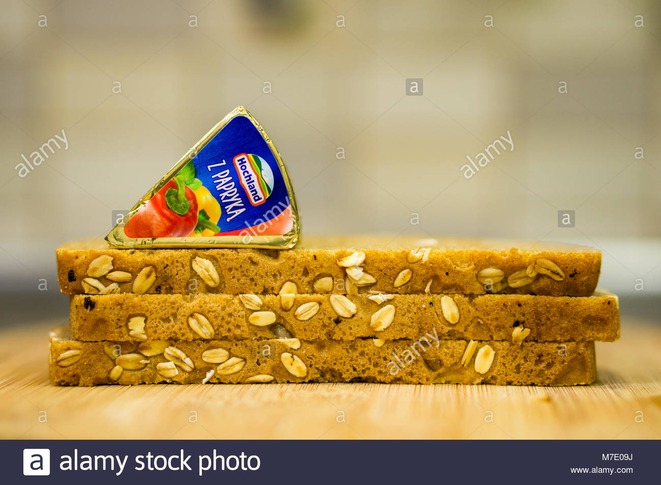 Poznan, Poland - March 07, 2018: Hochland cream cheese with red pepper on a pile of fresh bread in soft focus Stock Photo