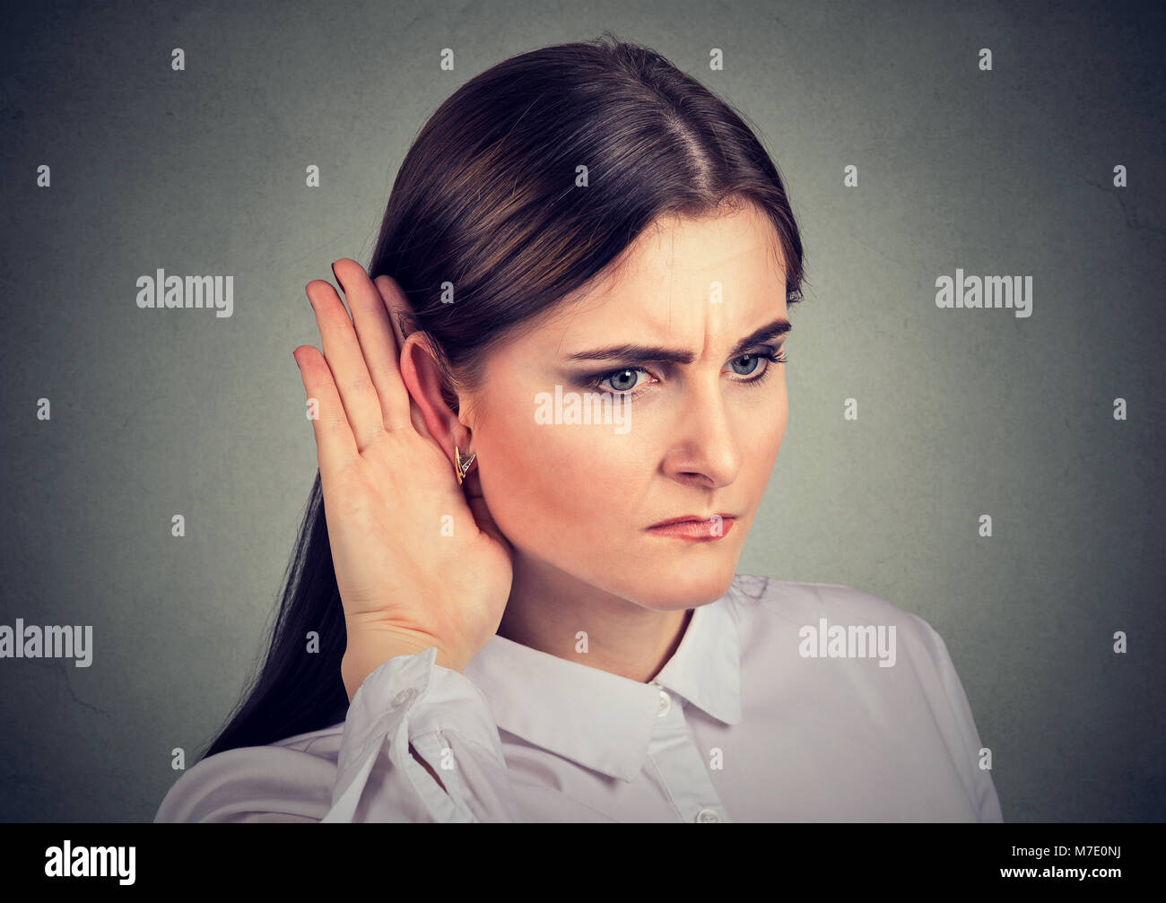 Young preoccupied girl having problems with hearing while listening to gossip. - Stock Image