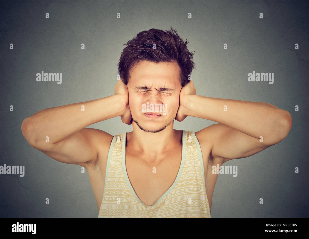 Young frustrated man covering ears annoyed with noise from neighbors. - Stock Image