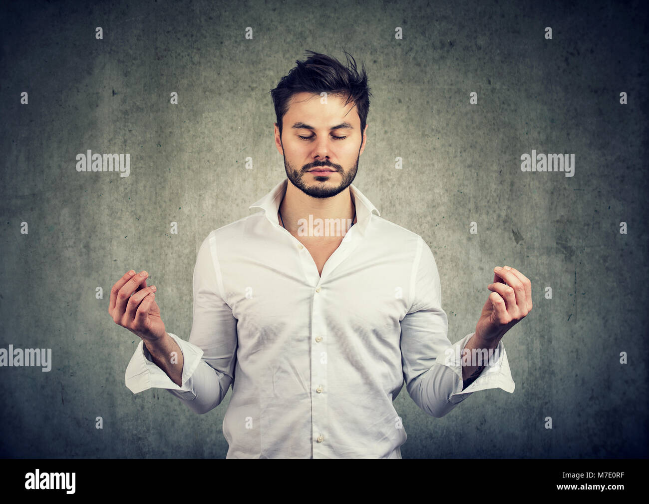 Handsome casual beard man holding hands in meditation and keeping eyes closed. - Stock Image