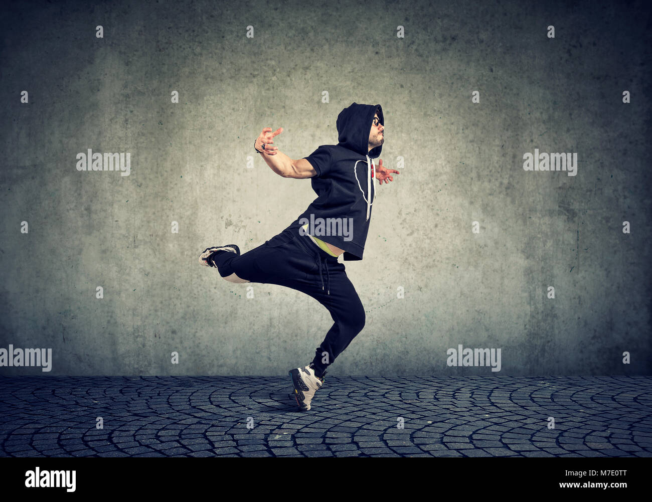 Stylish young man in trendy sportive clothing performing street dance with on gray wall background. - Stock Image