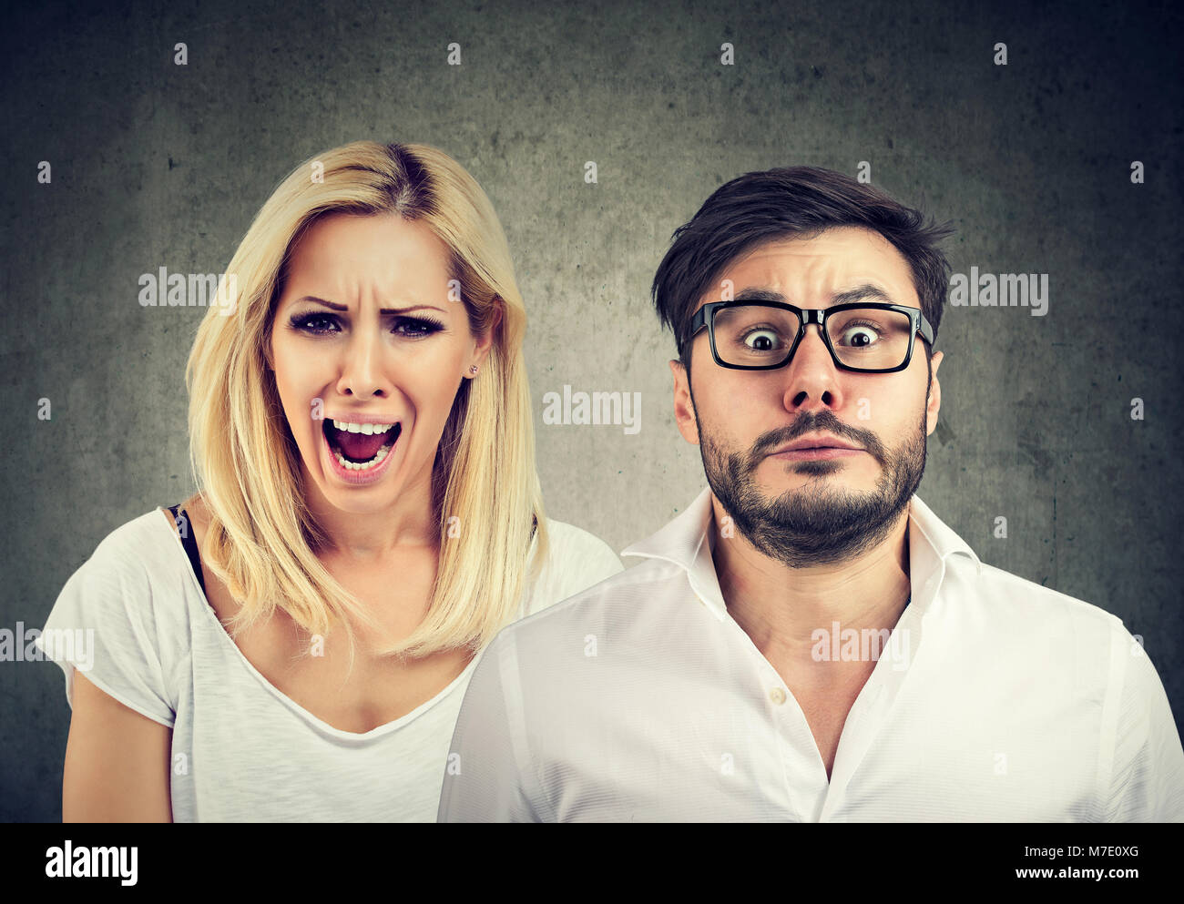 Angry mad woman screaming and fearful stressed man - Stock Image