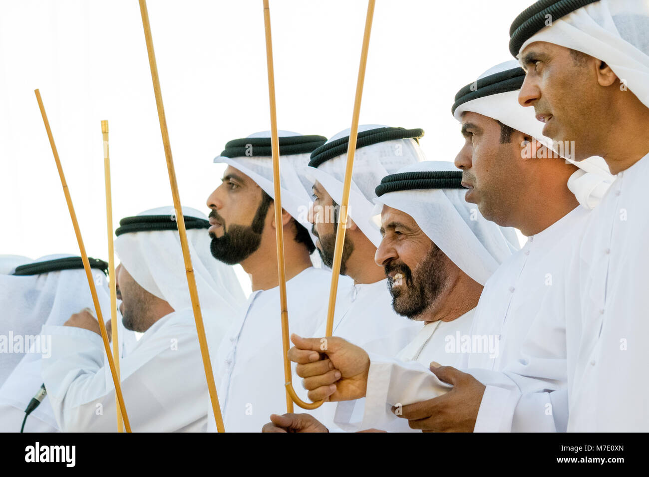 Emirati men pin traditional dress participating an an Ayala dance at the Sheikh Zayed Heritage Festival 2017 Stock Photo