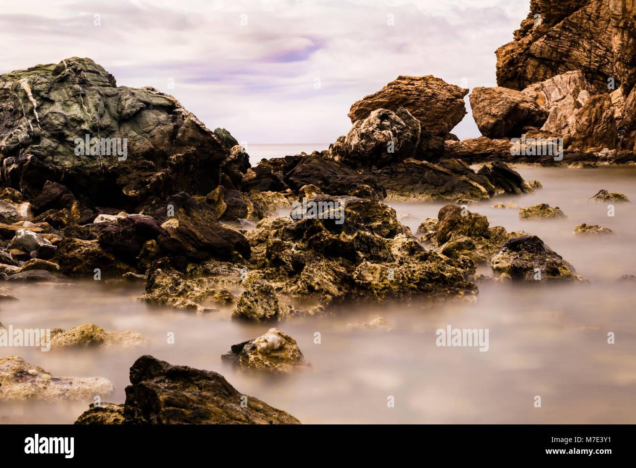 Long exposure of rocky coast in Greece, impressive rock formations on milky waters in sunrise light, landscape format, - Stock Image