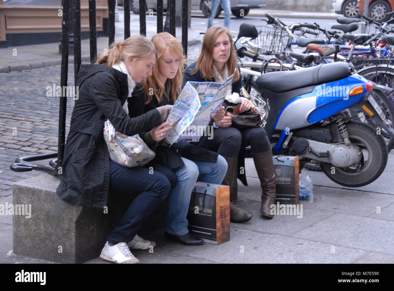 Three young tourists looking at the city map of Dublin in Temple Bar, Dublin in Southern Ireland - Stock Image