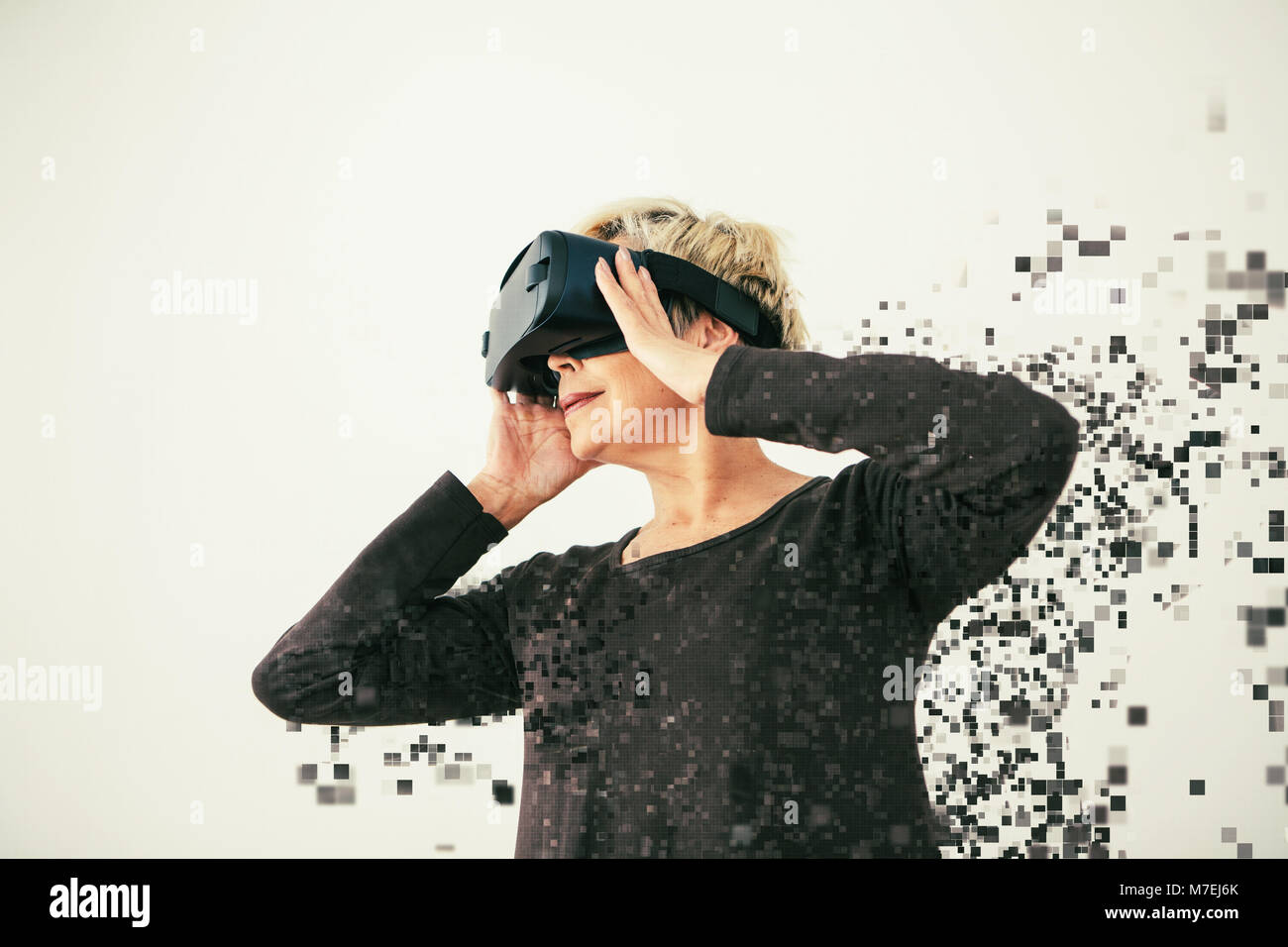 An elderly woman in virtual reality glasses is scattered by pixels. Conceptual photography with visual effects with - Stock Image