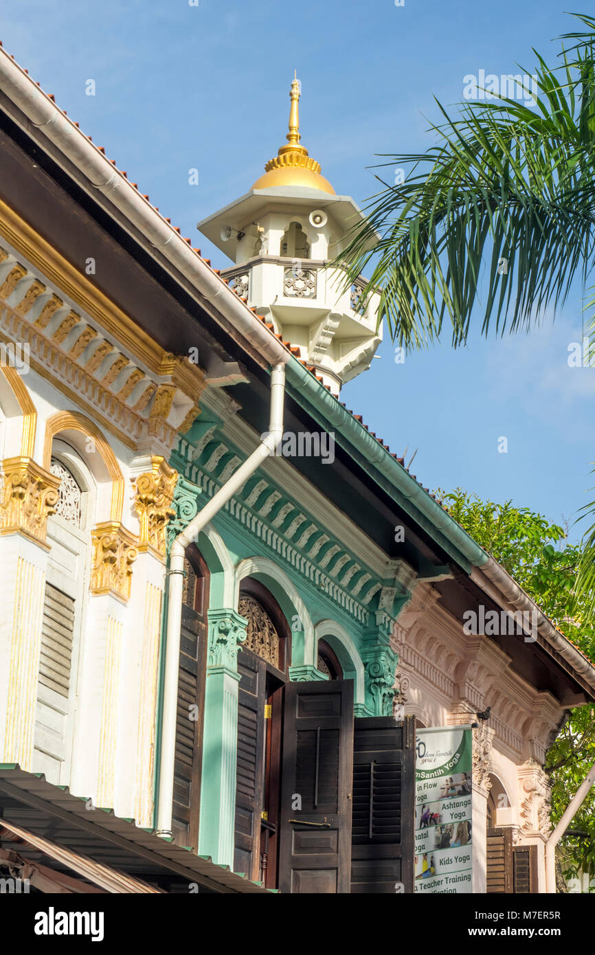 Row of shophouses and the Sultan Mosque's minaret in Singapore. - Stock Image