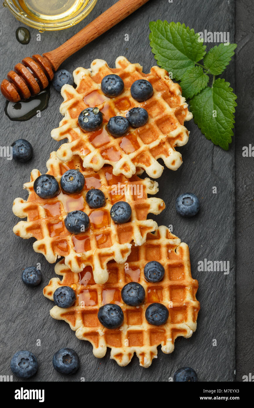Belgian  waffles with honey and fresh berries blueberry and mint on black surface. Delicious dessert - Stock Image