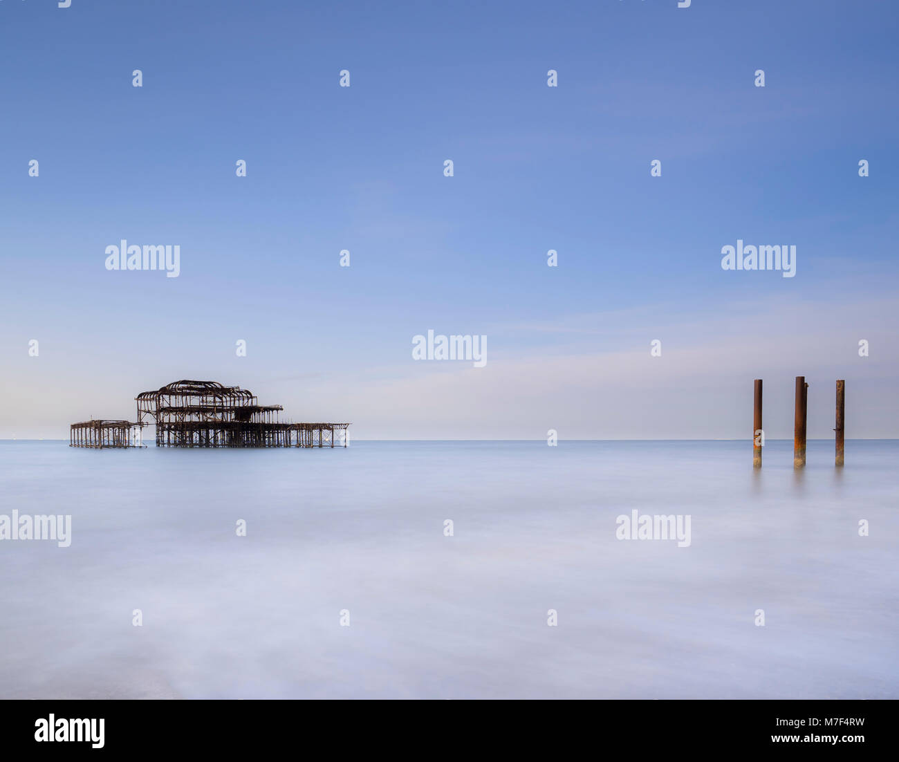 The old West Pier and what remains of the supporting posts at dawn. - Stock Image