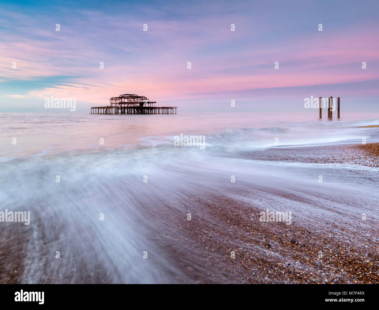Pink sky over the old west pier at sunrise. - Stock Image