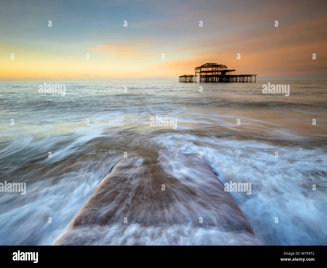 Water rushing over a stone jetty at the old Pier, Brighton. - Stock Image