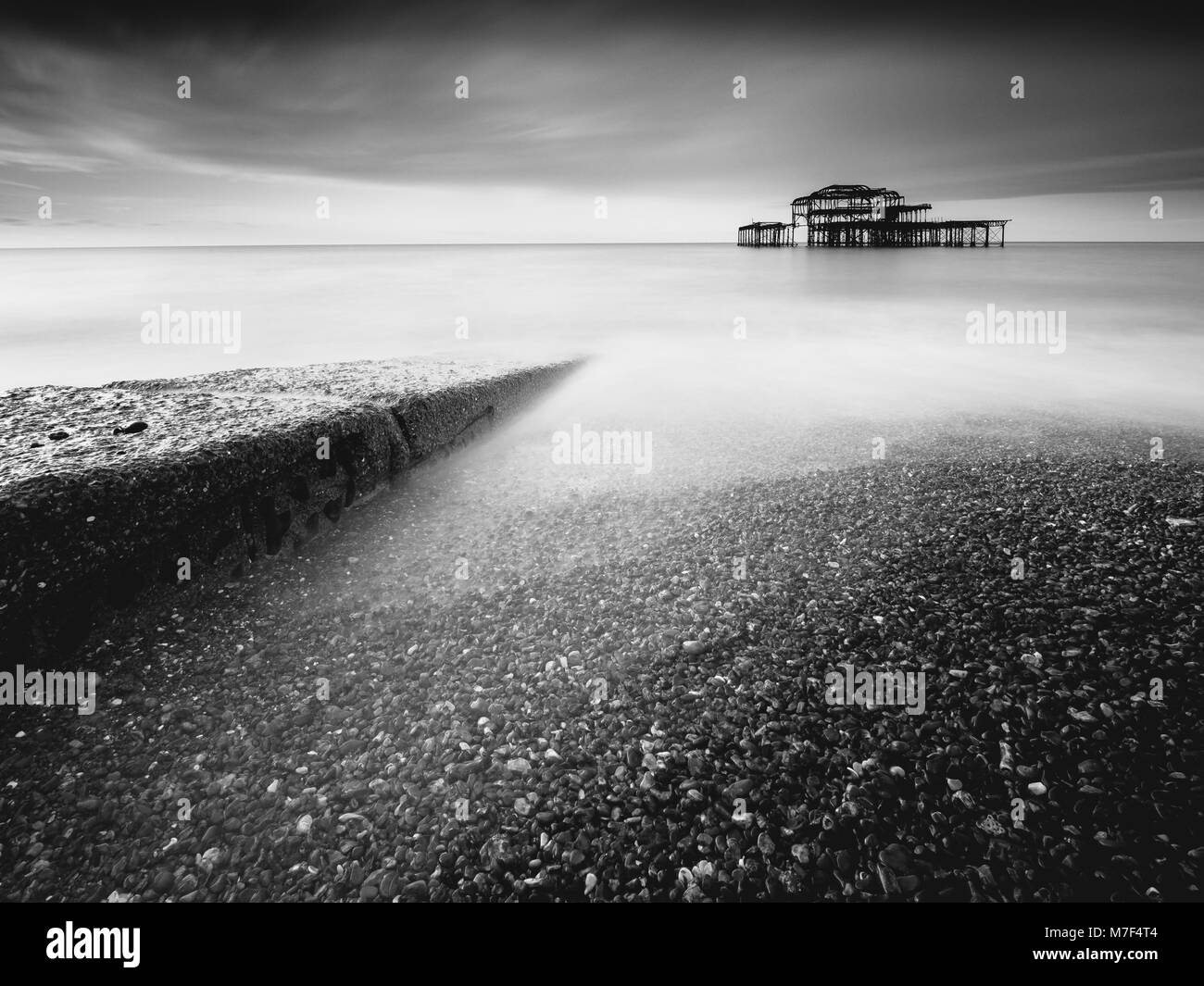 A stone jetty points towards the old ruined West Pier. - Stock Image