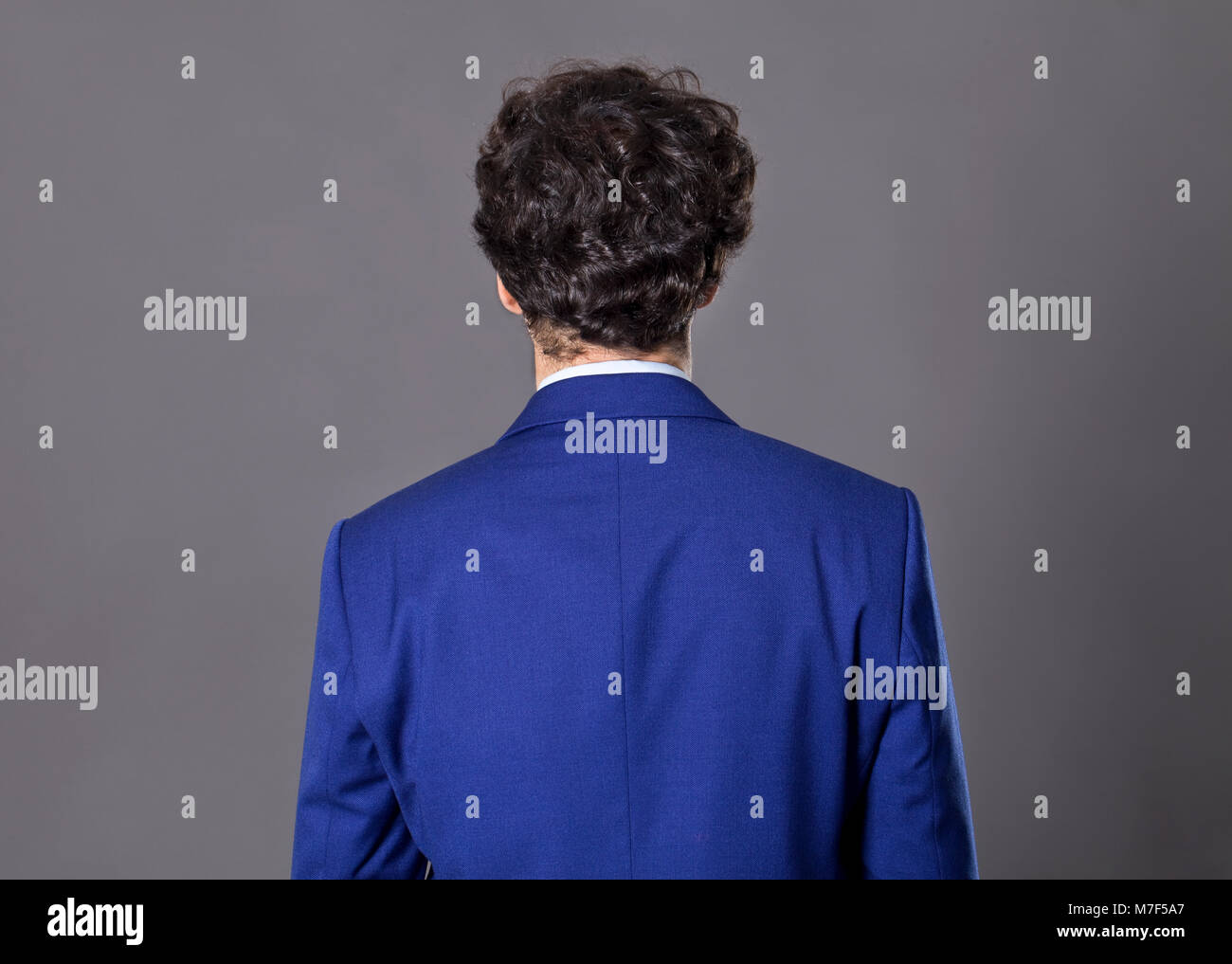 Young man with curly hair standing back to camera - Stock Image
