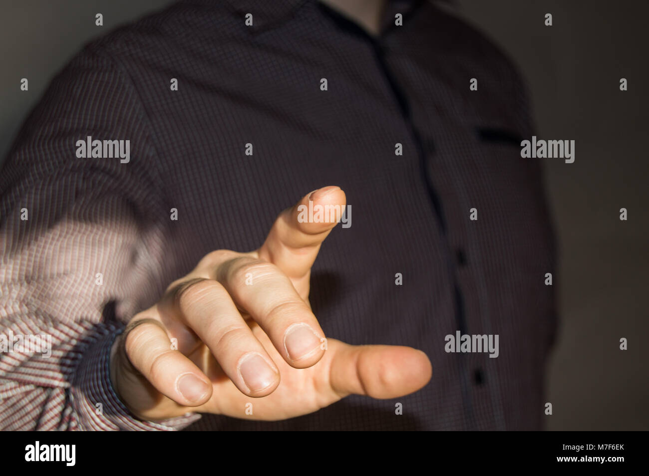 Businessman pointing finger at blank virtual screen by pressing virtual button - Stock Image