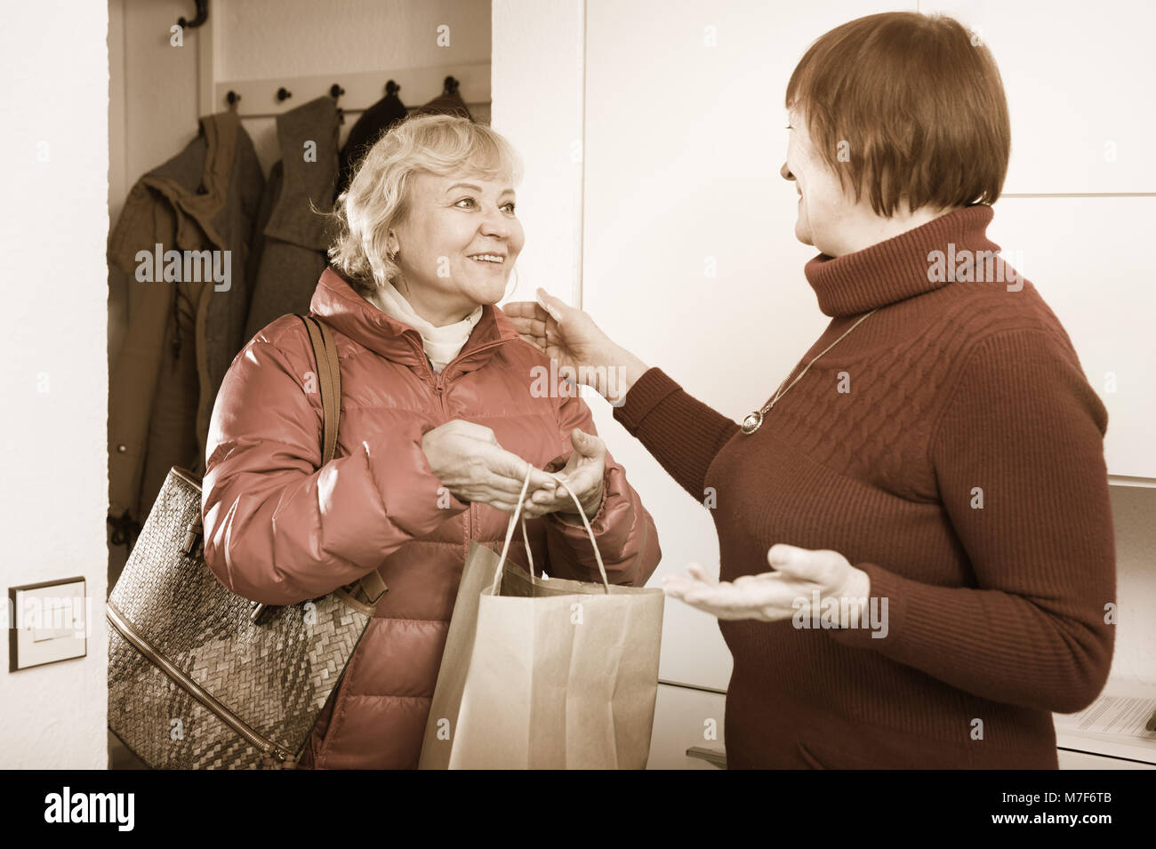 Positive old woman saying goodbye to friend female in jacket indoors - Stock Image