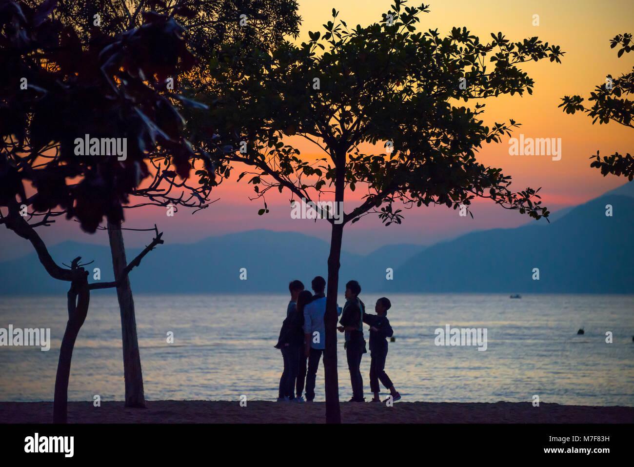 Children playing at Sunset, Repulse Bay, Hong Kong - Stock Image