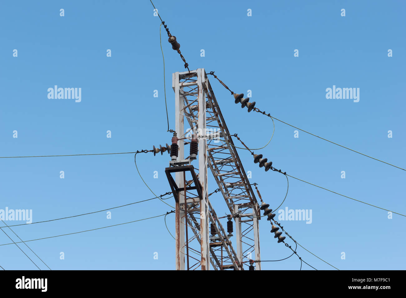 Train or railway power line support. Railway power lines with high voltage electricity on metal poles against blue - Stock Image