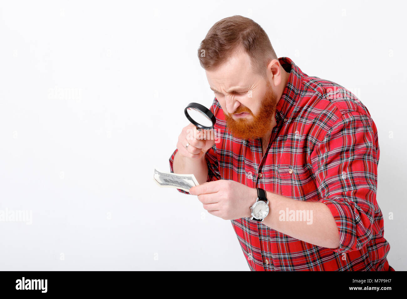 bearded man looking at magnifying glass for hundred dollar bill Stock Photo