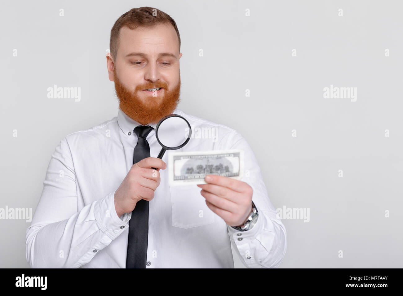 bearded male expert looking at magnifying glass for hundred dollar bill Stock Photo