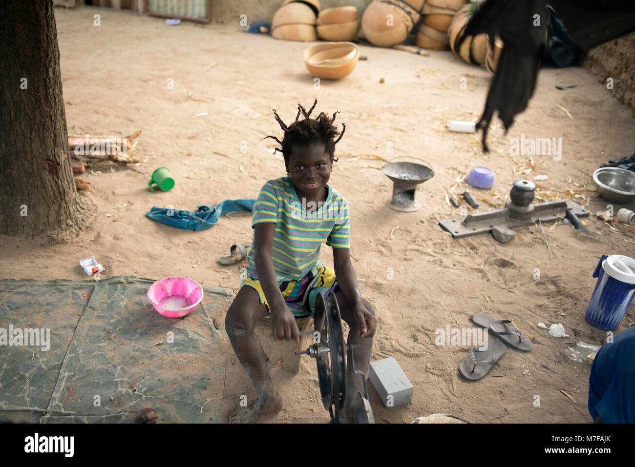 A young girl operates a wheel that drives bellows to fan the fire used to decorate calabashes. Segou, Mali, West - Stock Image