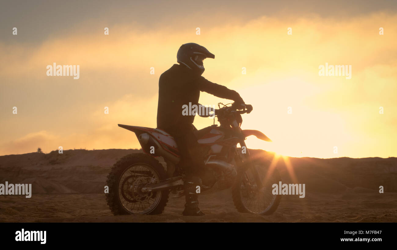 Professional FMX Motorcycle Rider Rests on His Bike and Overlooks Hard Sandy Off-Road Terrain. Sun is Setting. Stock Photo