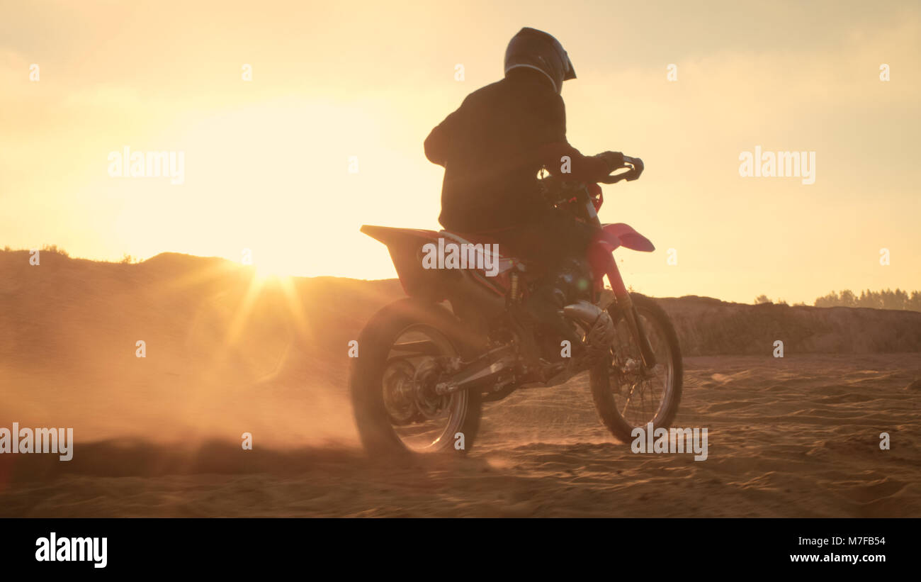 Professional FMX Motorcycle Rider Twists Full Throttle Handle and Starts Riding on the Sandy Off-Road Track. Scenic Stock Photo