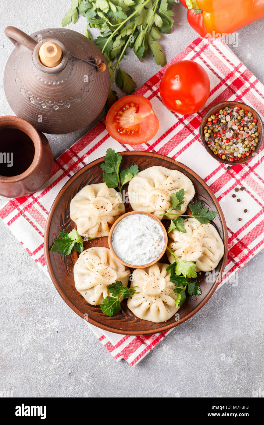 Khinkali - Georgian dumplings with meat and parsley in a ceramic dish with a sauce of sour cream and greens. Selective - Stock Image