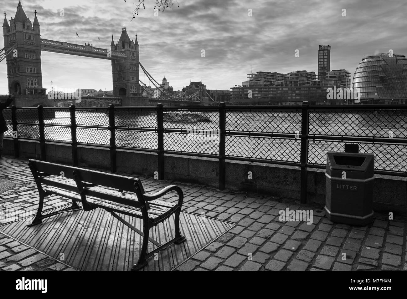 Black and white photo of a park bench facing Tower Bridge and the Thames at Sunrise - Stock Image