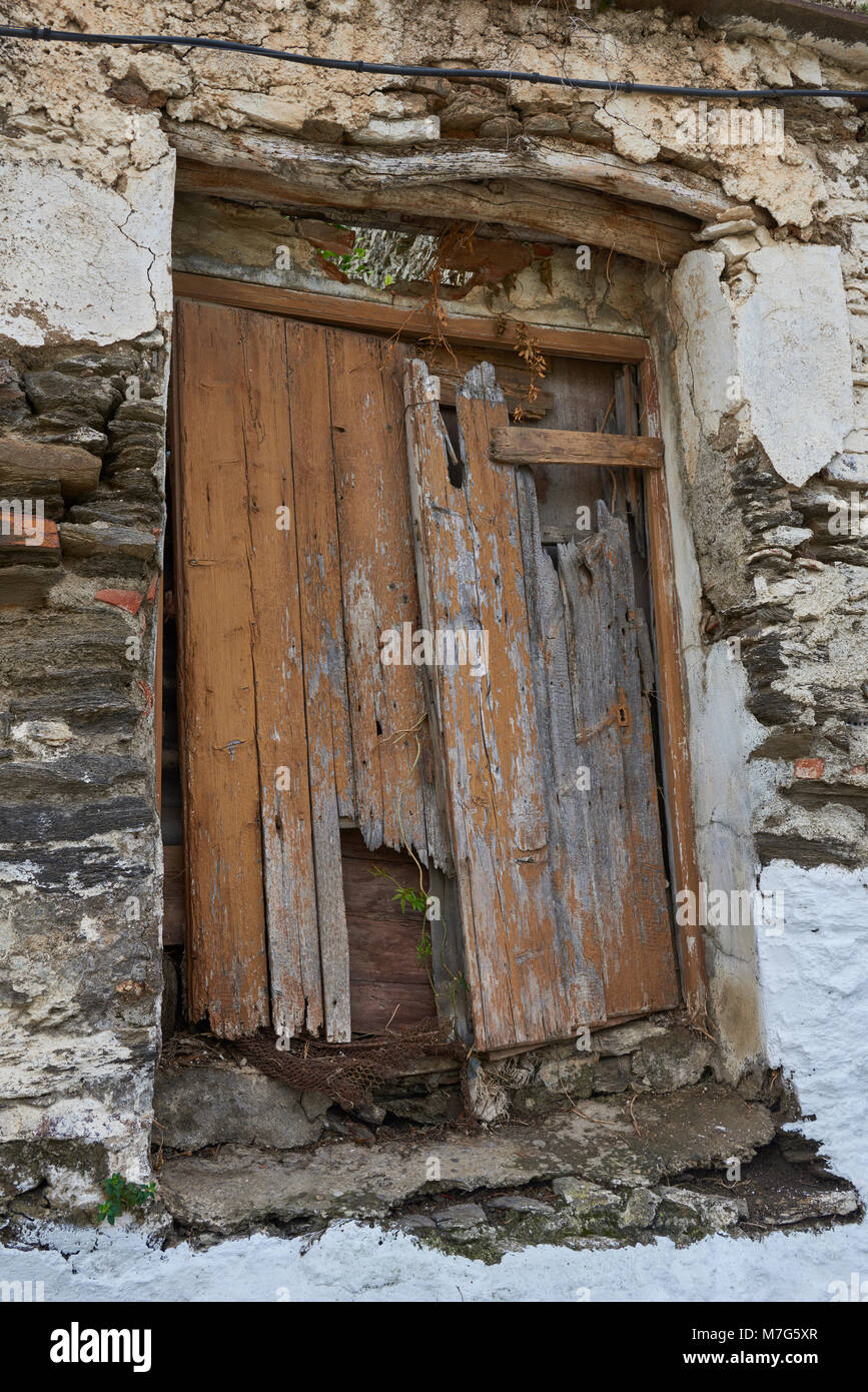 An Old Wooden Door With Lots Of Damage Visible On The Front Of An Abandoned  House