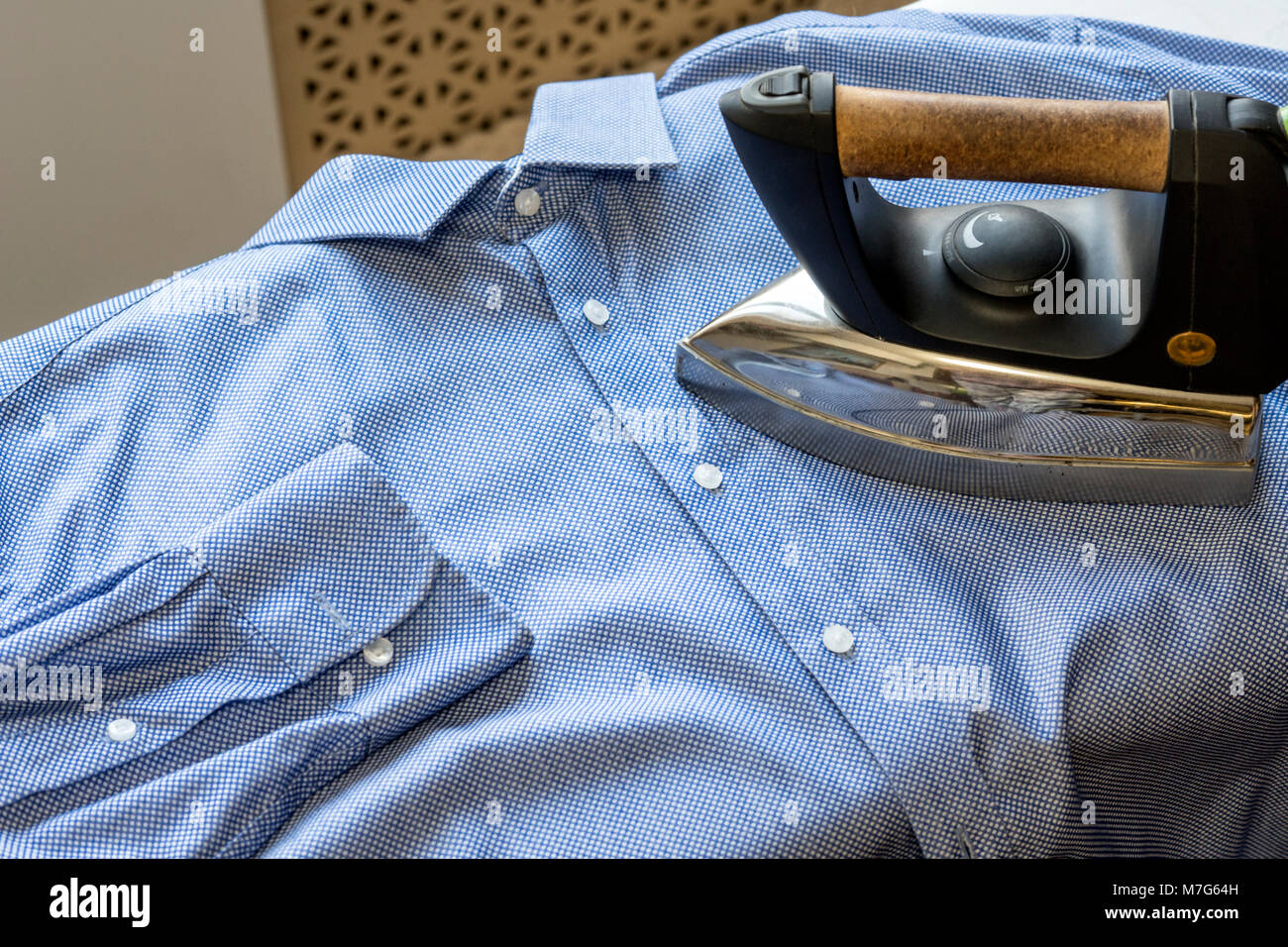 The iron strokes the man's blue shirt. Cleanliness and tidiness - Stock Image