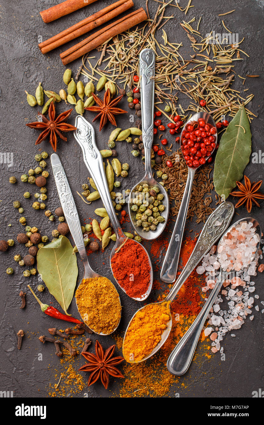 Variety of natural spices, seasonings and herbs in spoons on the stone table - paprika, coriander, cardamom, turmeric, - Stock Image