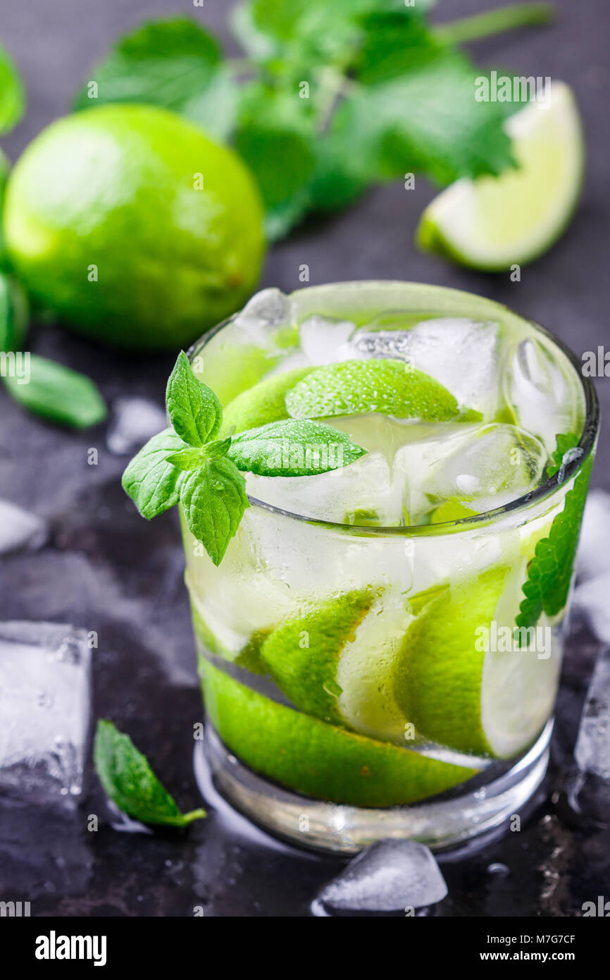Cold refreshing summer drink with lime, mint and ice cubes in a glass on a dark stone background. Mojito. Lemonade. - Stock Image